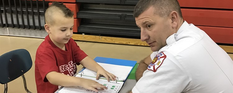 A Boyd County First Responder collaborates with a student.