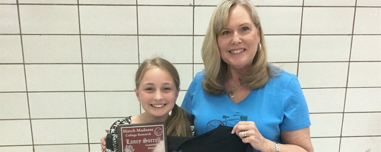 Laney, pictured at left, is awarded a plaque and t-shirt from School Counselor Theresa Kazee. Laney completed a voluntary college search that had her researching costs, admission requirements and majors for 3 different schools. Her winning essay can be read in the news article below.