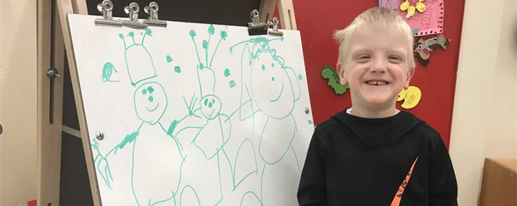 A preschool student gives a huge smile while standing in front of his newest creation.