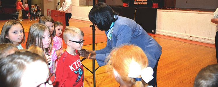 Lt. Governor Jenean Hampton stops to help a young student pin on a lapel pin. She spoke to an assembly of all of the students.