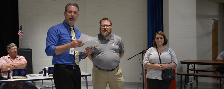 The high school choir was recognized for receiving a Distinguished Rating at the KY Music Educators Association's Assessment. Mr. Bowling, center, accepts a certificate along with a student representative from the choir.