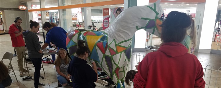 Mr. Spear's class of 17 art students painted one of the horses now on display at the Ashland Town Center mall. The picture shows the students working on the horse.