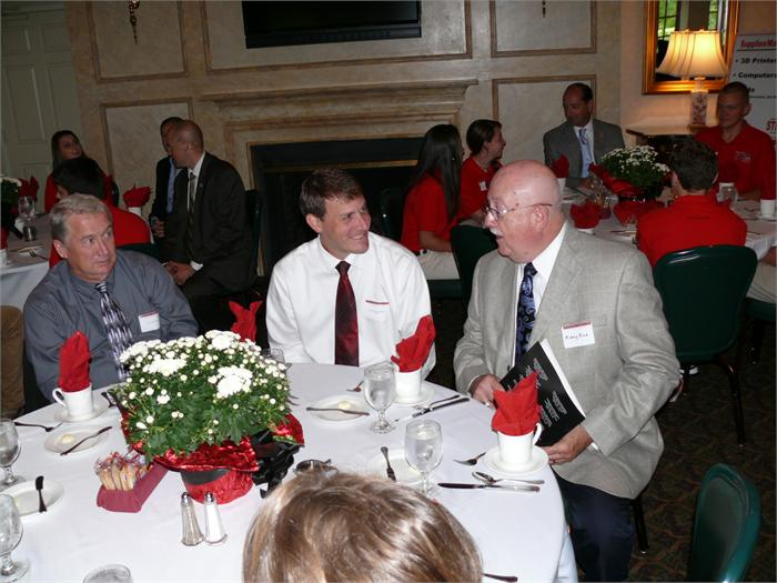 District Administrator Mickey Rice, far right, talks to a student and other area business leaders at the STEM luncheon.